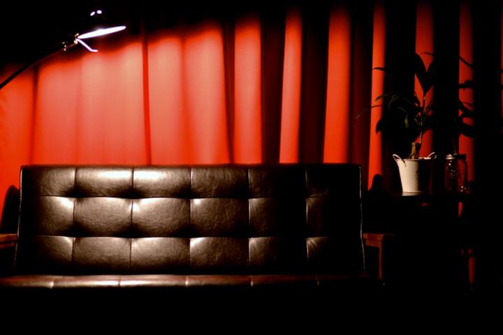 赤いカーテンと黒革のソファ